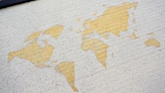 Laura Weingrill trägt zuerst die goldene Sprühfarbe auf die gesamte Korkplatte auf. Danach befestigt sie das Motiv (Kontinente) auf der getrockneten Platte und besprüht alles nochmals mit weißer Farbe. Zum Schluss wird das Motiv abgezogen