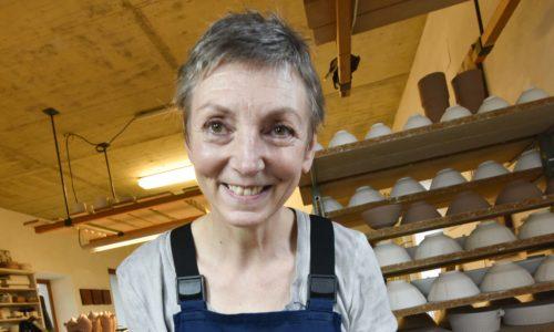 Eva Mayer hält ein frisches Töpferwerk, eine Vase, in Händen