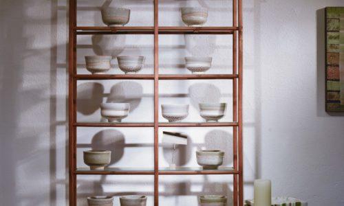 Ein Regal voll, aber schön arrangiert mit Töpferwerken von Eva Mayer